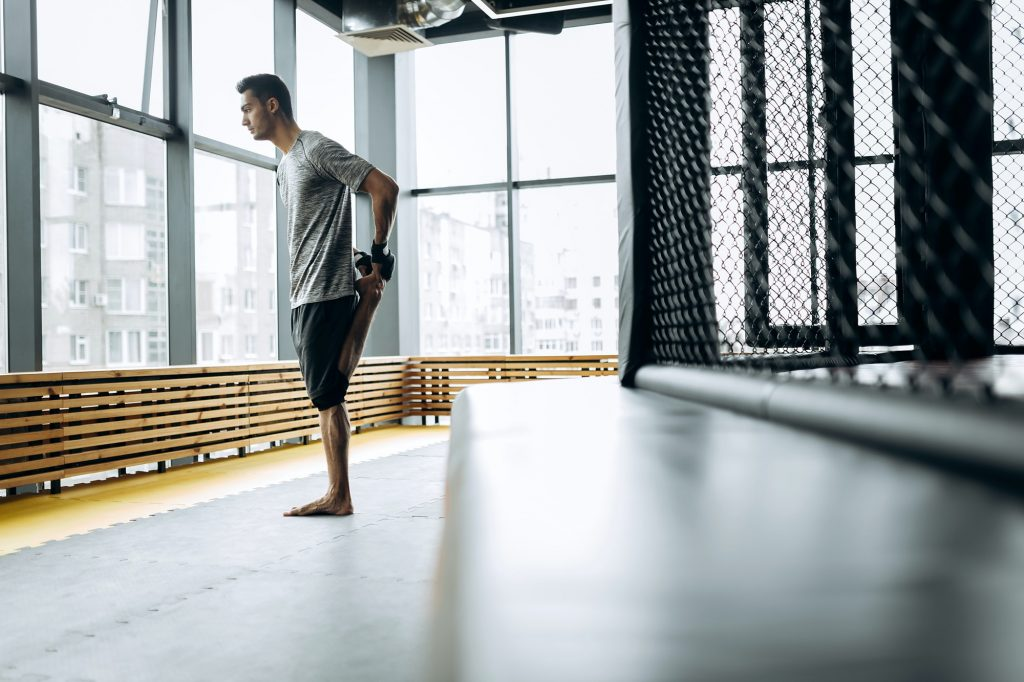 Guy dressed in the grey t-shirt stretches his arms in the boxing gym with panoramic windows